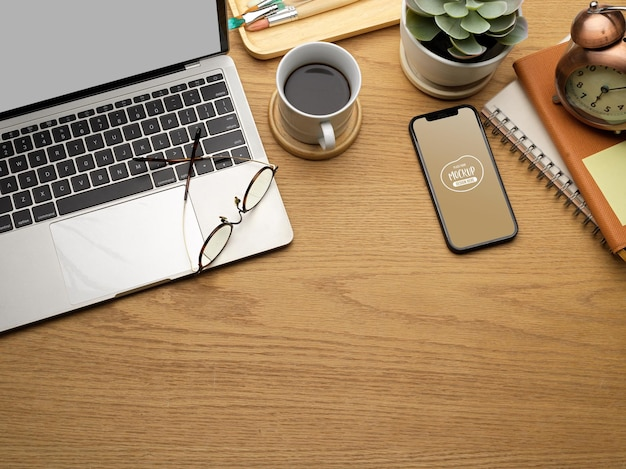 Top view of wooden workspace with smartphone, laptop, coffee cup, stationery, eyeglasses and copy space