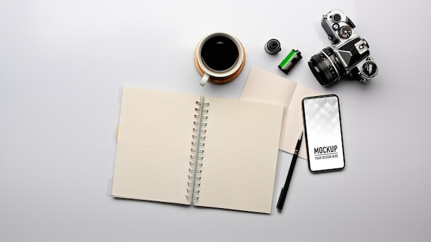 Top view of workspace with blank notebook, smartphone mockup