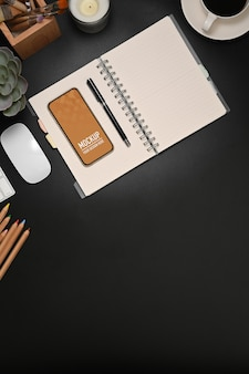 Top view of workspace with blank notebook, stationery, smartphone mockup