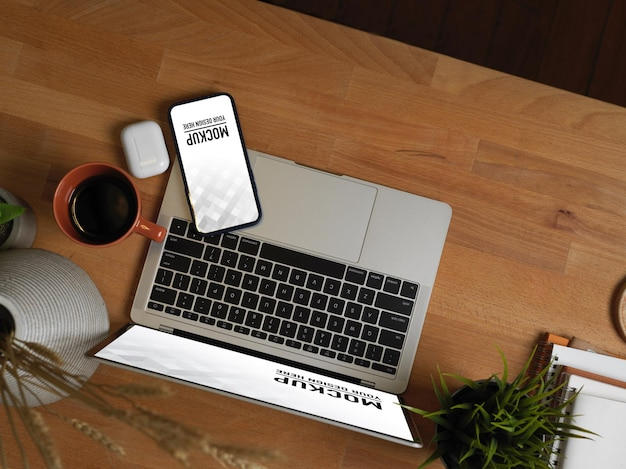 Top view of workspace with laptop, smartphone mockup