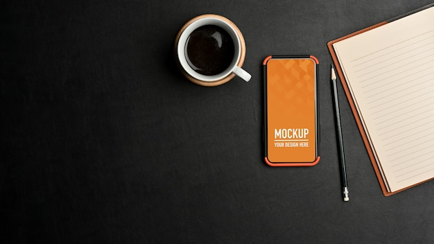Top view of workspace with smartphone mockup, notebook and pencil