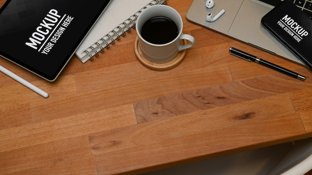 Top view of workspace with smartphone and tablet mockup and office supplies