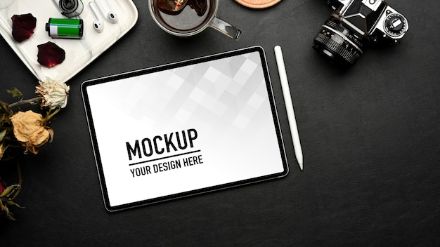 Top view of workspace with tablet mockup, supplies and decorations on black table