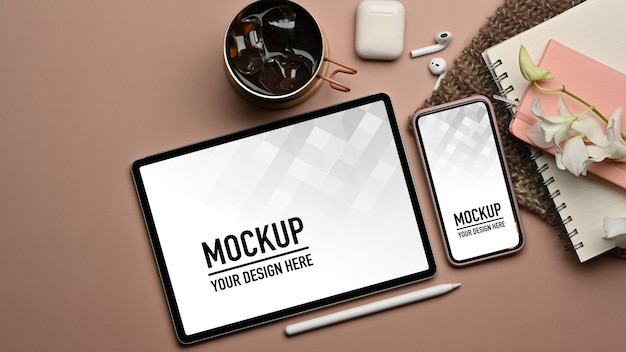 Top view of workspace with tablet and smartphone mockup and stationery