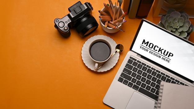 Top view of worktable with laptop mockup, coffee cup, camera, supplies