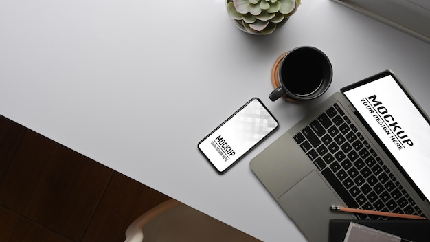 Top view of worktable with laptop, smartphone mockup