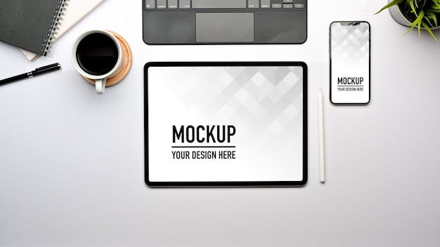 Top view of worktable with tablet and smartphone mockup