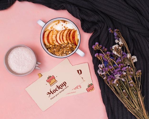 Вид сверху йогурт и фрукты с картонным макетом и мертвыми цветами