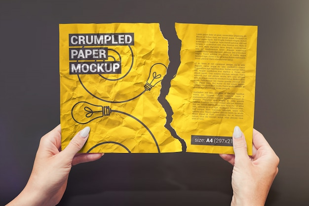 Torn and crumpled paper in hands mockup