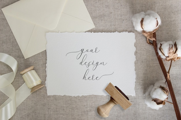 綿の花とシルクリボンのリネンの布に引き裂かれたエッジカード。結婚式の文房具のモックアップ。招待