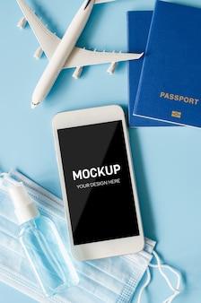 Планирование путешествий и туризма после карантина. смартфон с моделью самолета, паспорта, маска для лица и дезинфицирующее средство.