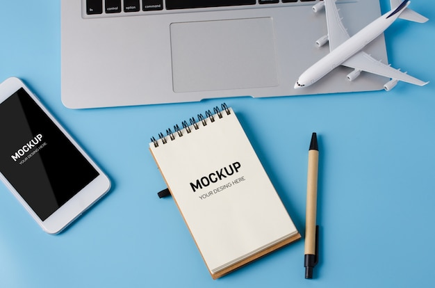 Travel booking with laptop, notebook, smartphone and airplane model on blue table.