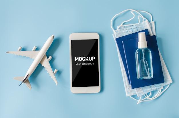 旅行計画のコンセプトとコロナウイルス。飛行機モデルのフェイスマスクと消毒スプレーを備えたスマートフォンのモックアップ。