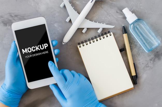 旅行計画のコンセプト、コロナウイルス、検疫。使い捨て手袋の手がスマートフォンを持ち、ノートに書き込みます。コピースペースで模擬。飛行機モデル、フェイスマスク、手の消毒スプレー。