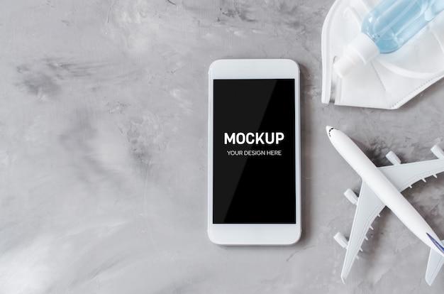 旅行計画のコンセプト、コロナウイルス、検疫。飛行機のモデル、フェイスマスク、手の消毒スプレーが付いたスマートフォンのモックアップ。コピースペースの平面図。