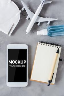 旅行計画のコンセプト、コロナウイルス、検疫。ノートブックと飛行機のモデルでスマートフォンのモックアップ。コピースペースの平面図。フェイスマスクと手指消毒スプレー。