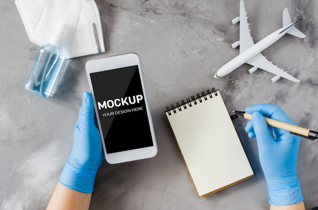 Travel planning concept, coronavirus and quarantine. hands in disposable gloves hold smartphone and write in notebook. mock up with copy space. airplane model, face mask and hand sanitizer spray.