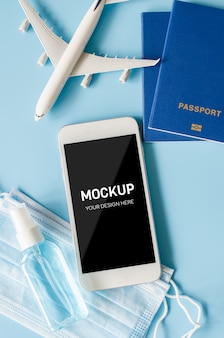 Travel and tourism planning after quarantine. smartphone with airplane model, passports, face mask and sanitizer.