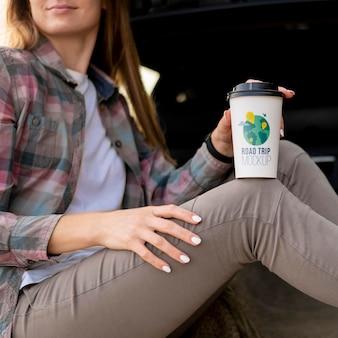 コーヒーのモックアップカップを保持している旅行者