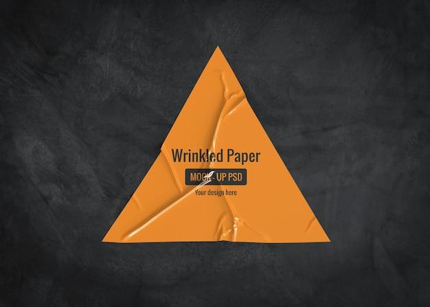 暗い表面の三角形のしわのある紙のモックアップ