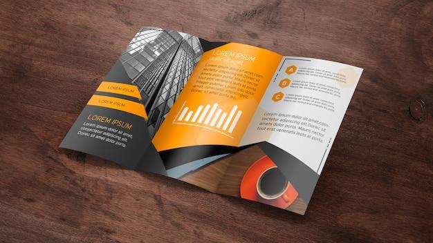 Modello di brochure a tre ante su superficie in legno