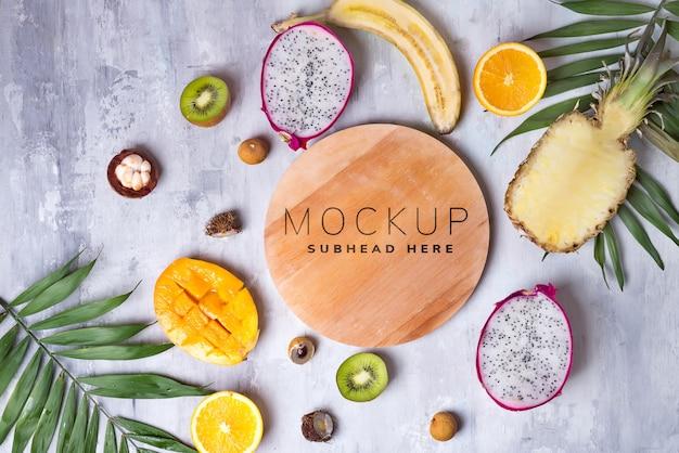 Тропические фрукты с деревянной тарелкой макет
