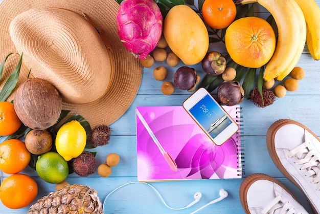 Tropical hat, many fruits on blue wooden background