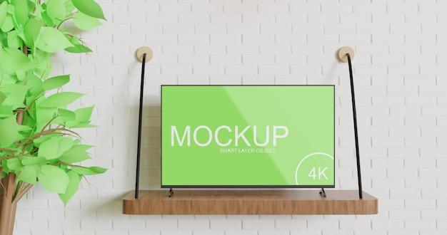 木製の壁テーブルの上にテレビモックアップ立って