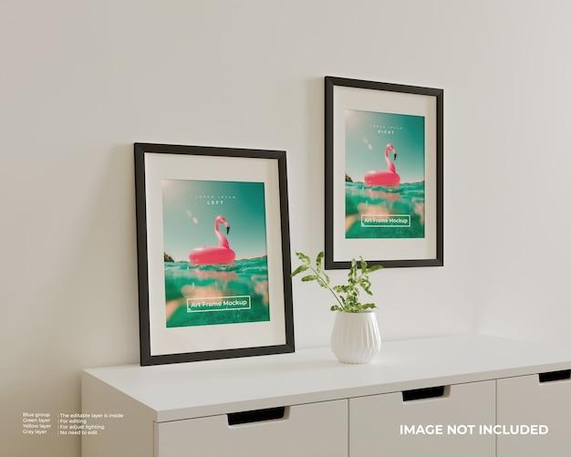 白い食器棚の上に2つのアートフレームポスターモックアップ