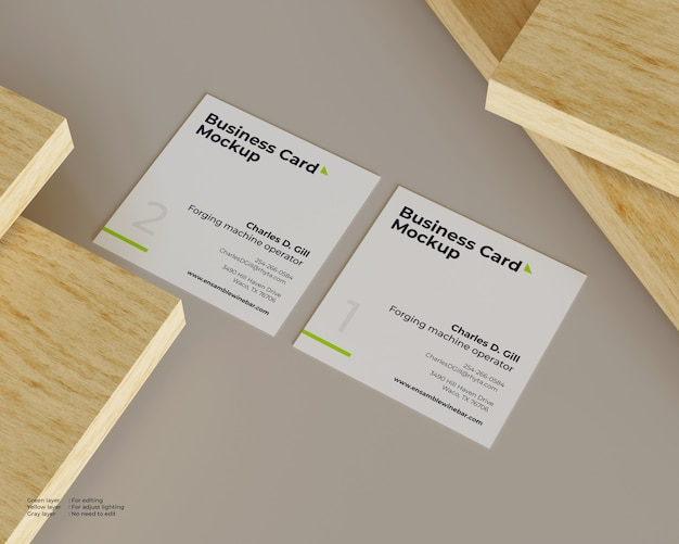 Two business cards mockup are under a pile of wood