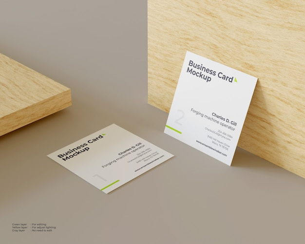 Two business cards mockup one of which leaned against the wood