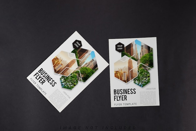 Two flyers mockup on black table, top view