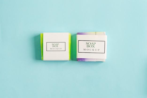 Два мыла ручной работы обернуть коробку макет пакета с красочными мыло бар, изолированных на синем фоне