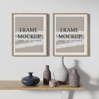 Two poster frames above ceramic vases