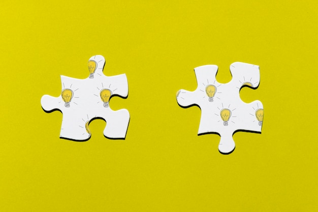 Two puzzle pieces on yellow background