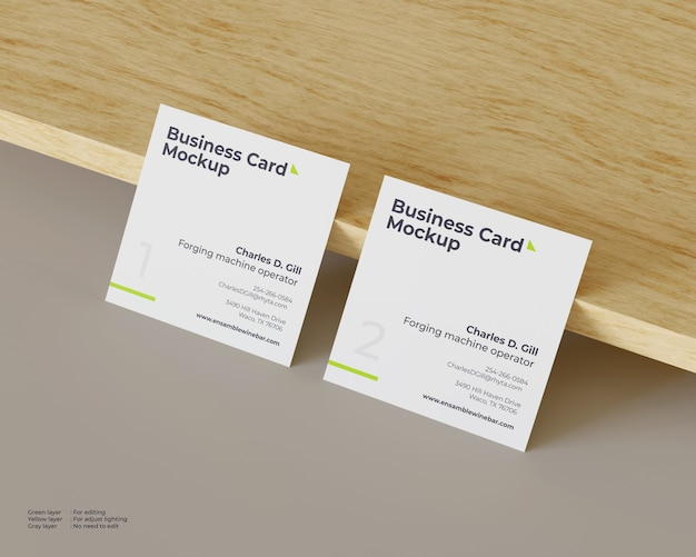 Two square business cards mockup lean against wood