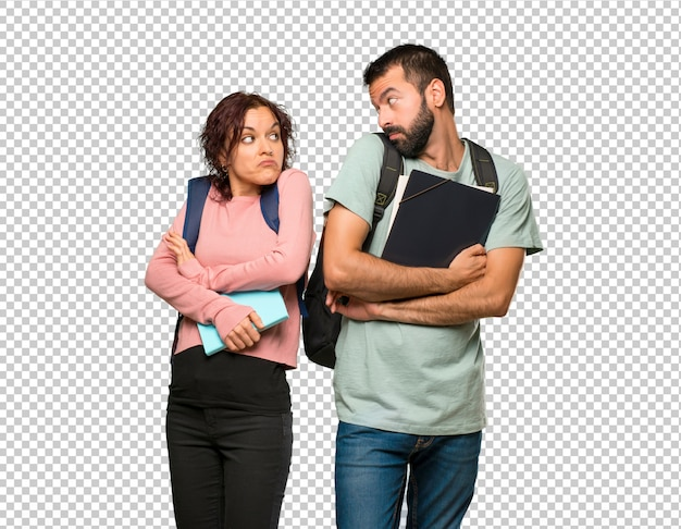 Two students with backpacks and books making unimportant gesture while lifting the shoulders