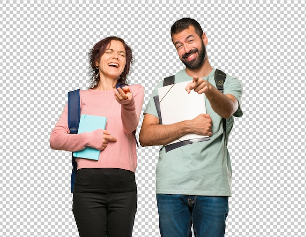 Two students with backpacks and books pointing with finger at someone and laughing a lot