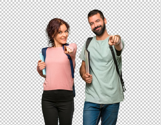 Two students with backpacks and books points finger at you with a confident expression