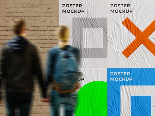 都市の広告の壁は、人々が見ているレンガの壁に通りのポスターのモックアップを接着しました