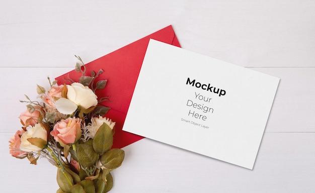 木製のテーブルにバレンタインデーのグリーティングカードのモックアップと手紙と花
