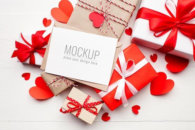 Макет карты дня святого валентина с подарочными коробками и красными бумажными сердечками