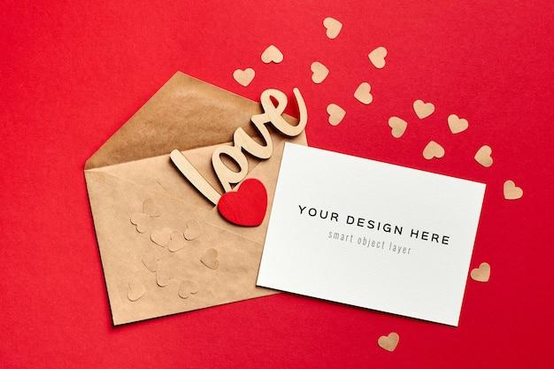 Макет карты дня святого валентина с конвертом и деревянными украшениями, любовью и сердцем на красном