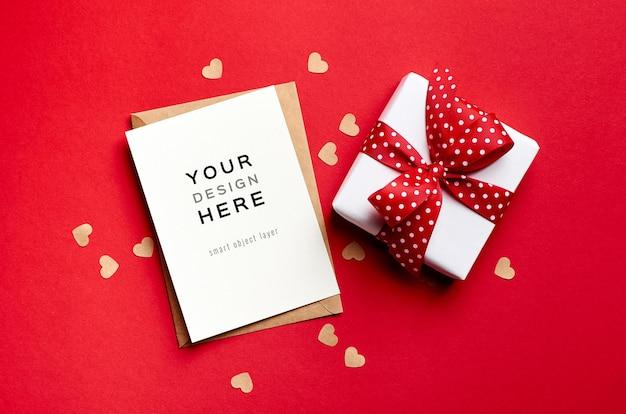 Макет карты дня святого валентина с подарочной коробкой и маленькими бумажными сердечками на красном
