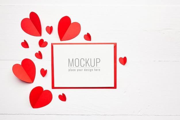 흰색 나무 표면에 빨간 종이 마음으로 발렌타인 데이 카드 모형