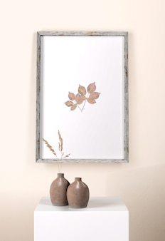 Vases with flowers and frame on wall