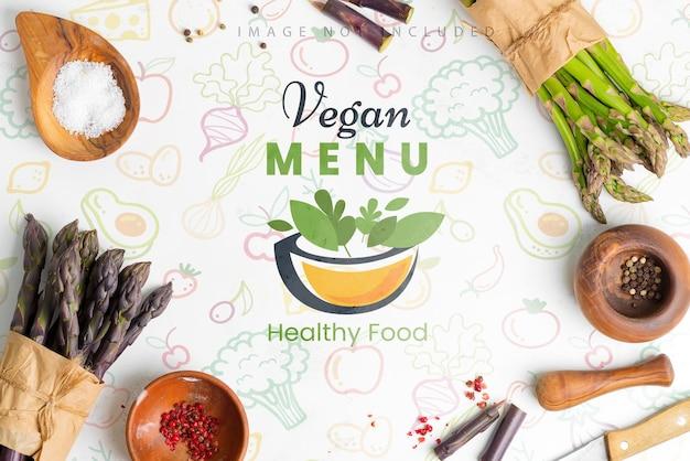 Поверхность овощей из двух пучков свежесобранной органической натуральной спаржи и ингредиентов для приготовления домашних диетических блюд на светло-серой поверхности. копировать пространство вид сверху