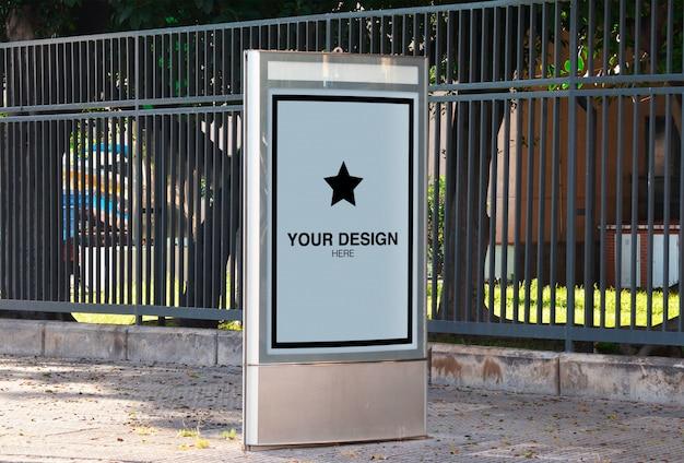 Вертикальный макет рекламного щита на тротуаре с парком на фоне