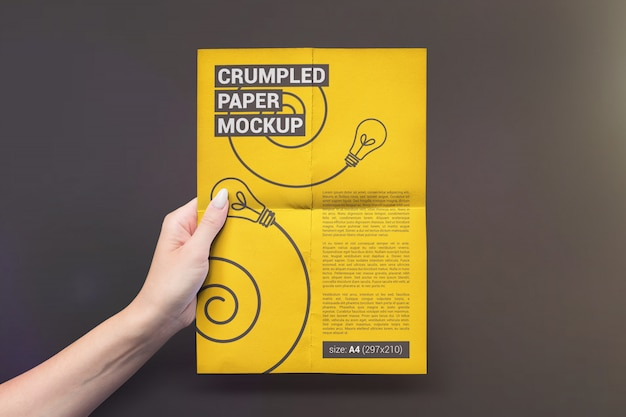 Vertical folded paper in hand mockup