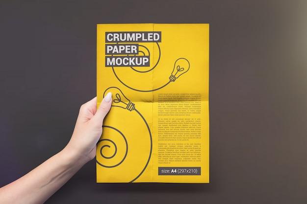 Вертикально сложенная бумага в руке макет